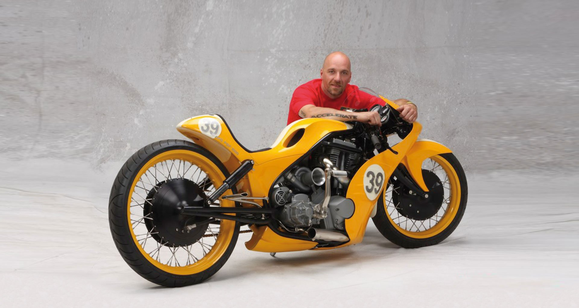 Goldammer, posiblemente el más polifacético constructor de motocicletas personalizadas del mundo, abrazado a una de sus creaciones: la Goldmember
